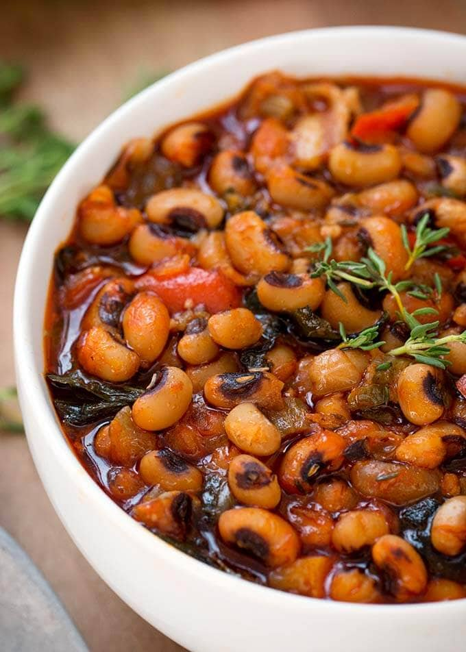 Instant Pot Black Eyed Peas is a delicious, traditional meal for New Year's. Make these Black-Eyed Peas with collard greens in your pressure cooker. Quick cooking! simplyhappyfoodie.com #instantpotrecipes #instantpotblackeyedpeas #instantpotbeans #instantpotcollardgreens