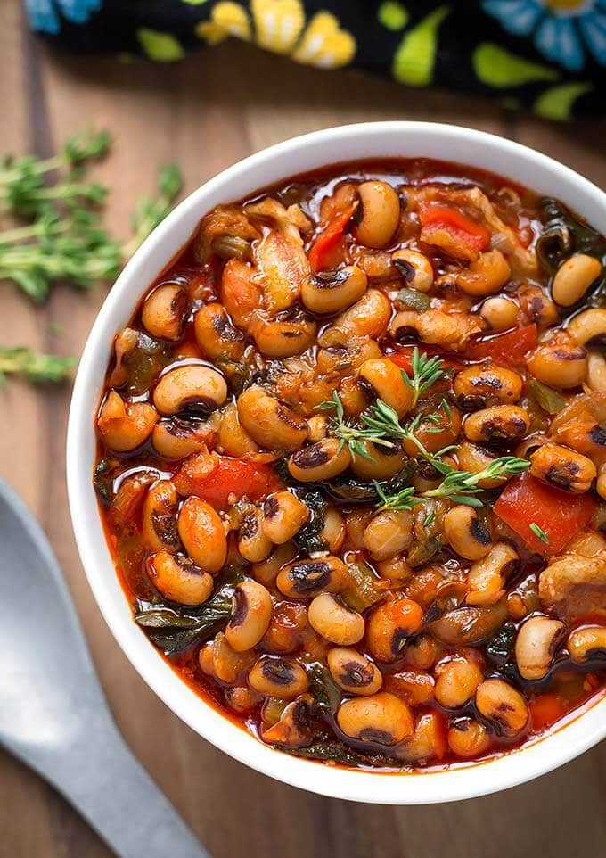 Instant Pot Black-Eyed Peas is a delicious, traditional meal for New Year's. Make these Black Eyed Peas with collard greens in your pressure cooker. Quick cooking! simplyhappyfoodie.com #instantpotrecipes #instantpotblackeyedpeas #instantpotbeans #instantpotcollardgreens
