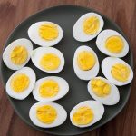 Boiled Eggs cut in half on black plate on wood board
