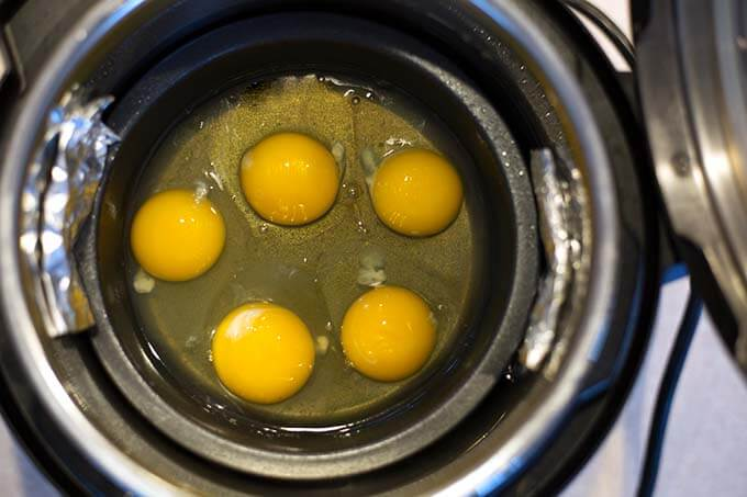 Five cracked eggs in small round pot for PIP cooking in pressure cooker