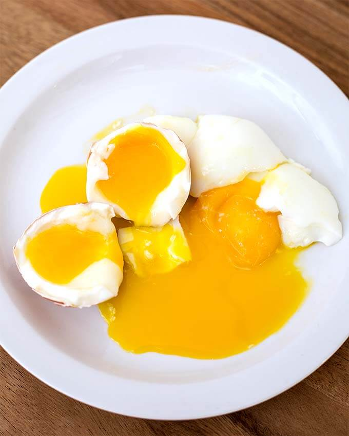 Two under cooked Boiled Eggs cut in half on white plate on wooden board