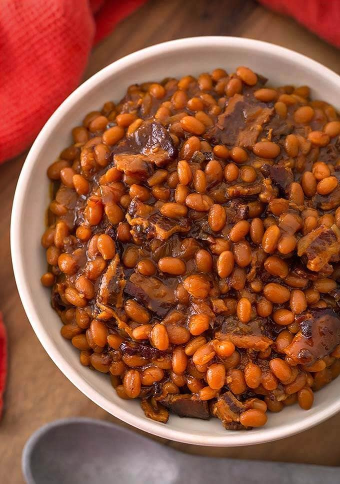 Smoky Sweet Baked Beans in a white bowl on wooden board