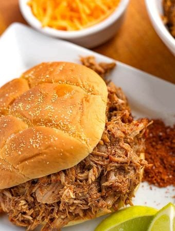 Pulled Pork on hamburger bun on a square white plate