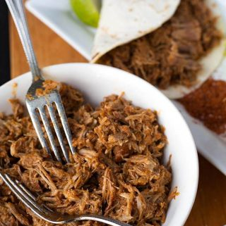 Instant Pot Pulled Pork is flavorful and very tender pork shoulder that you can shred for sandwiches, tacos, over rice or potatoes. Pressure cooker pulled pork. simplyhappyfoodie.com #instantpotpulledpork #pressurecookerpulledpork #instantpotrecipes #pressurecookerrecipes