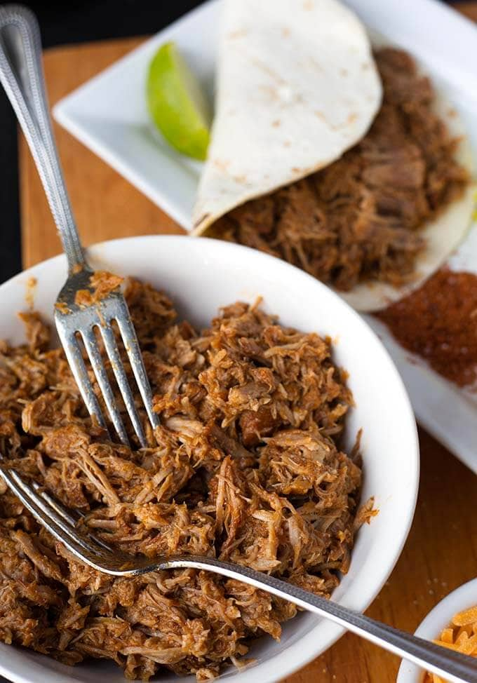 Instant Pot Pulled Pork is flavorful and very tender pork shoulder that you can shred for sandwiches, tacos, over rice or potatoes. Pressure cooker pulled pork. simplyhappyfoodie.com #instantpotpulledpork #pressurecookerpulledpork #pressurecookerrecipes