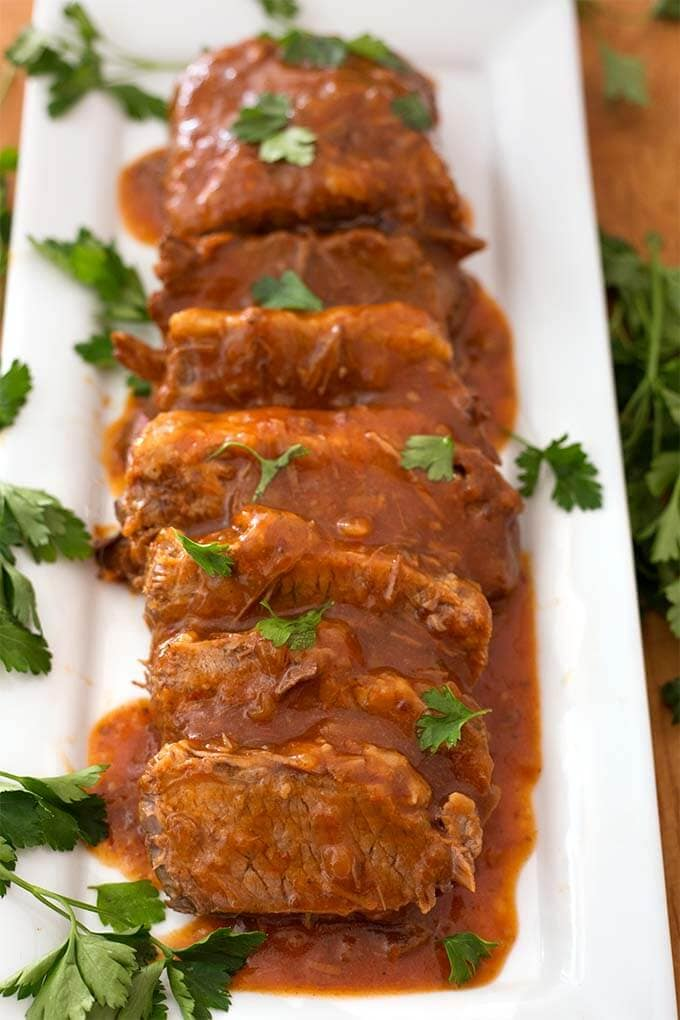 Sliced Saucy Beef Brisket on white rectangular platter garnished with green herb