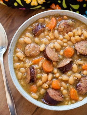 Sausage and White beans om a gray bowl next to silver spoon on wooden board