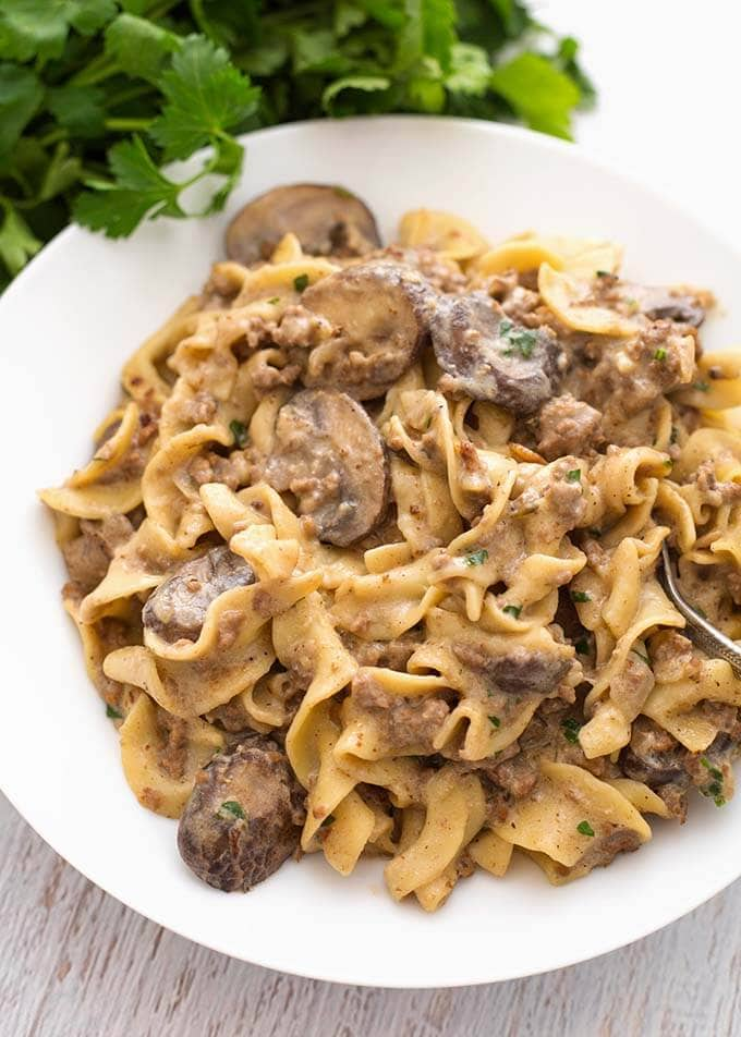 Hamburger Stroganoff on a white plate with fork next to bunch of parsley
