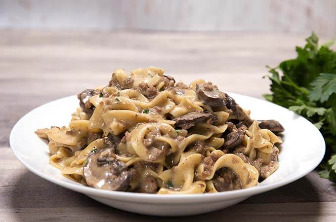 Instant Pot Hamburger Stroganoff is a delicious, money saving variation of the favorite Beef Stroganoff. With a rich flavor, no 'cream of' soup needed, this pressure cooker stroganoff will become a family favorite! simplyhappyfoodie.com #instantpotbeefstroganoff #instantpothamburgerstroganoff #pressurecookerstroganoff