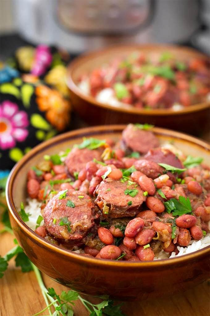 Two brown bowls of Red Beans and Rice With Sausage on wooden board in front of pressure cooker