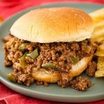 Sloppy Joes on hamburger bun next to chips all on blue plate