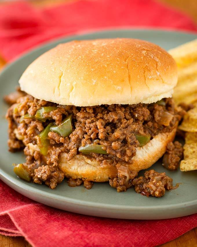 Sloppy Joes on hamburger bun next to chips all on blue green plate