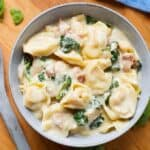 pressure cooker Tortellini Alfredo in grey bowl on wooden board