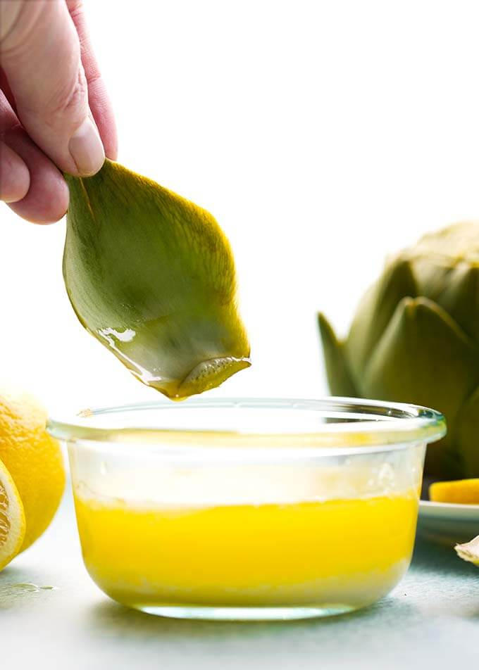 hand dipping part of artichoke into a small bowl of melted butter
