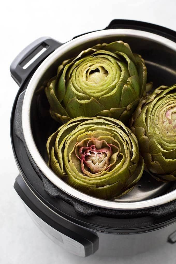 Instant Pot Whole Steamed Artichokes are a faster and easier way to cook artichokes. Pressure cooker artichokes are tender and ready to dip in your favorite sauce! simplyhappyfoodie.com #instantpotrecipes #instantpotartichokes #instantpotsteamedartichokes #instantpotwholeartichoke #pressurecookerartichoke #steamedartichokes