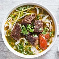 Vietnamese Beef Stew Pho Noodle Soup in a white bowl