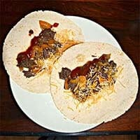 Two Instant Pot Beef Carnitas on tortillas and a white plate