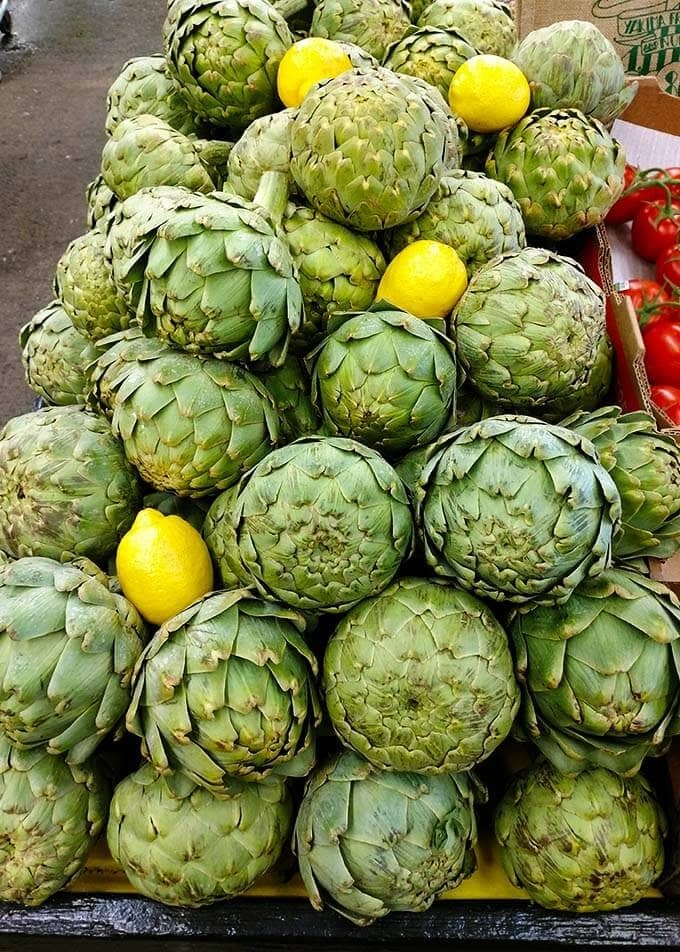 Several Artichokes stacked up with lemons at the Farmers Market