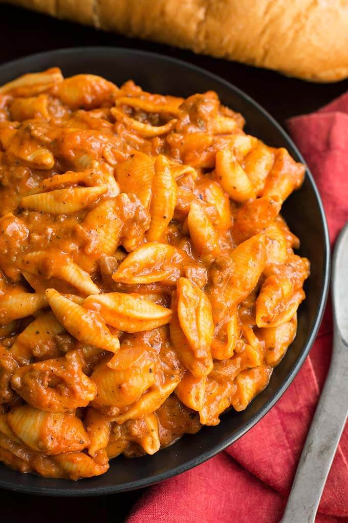 Instant Pot Cheesy Meaty Shells taste almost like a bowl of lasagna pasta! Rich tomato flavor makes the meat sauce delicious. Two kinds of cheese take this pressure cooker Italian pasta dish over the top! simplyhappyfoodie.com #instantpotrecipes #inatantpotpasta #instantpotlasagnapasta #pressurecookeritalianpasta