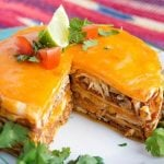 Instant Pot Chicken Taco Pie is fun and easy to make. Layers of chicken, beans, cheese, and tortillas are cooked together to make a delicious dinner. Make this pressure cooker taco pie with pantry ingredients you probably already have! simplyhappyfoodie.com #instantpotrecipes #instantpottacopie #instantpotchickentacopie #pressurecookertacopie