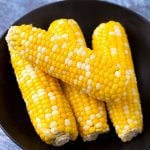 Four Corn on the Cobs on a black plate