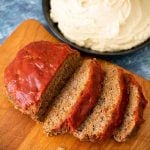 Sliced Meatloaf on a wooden cutting board with a black bowl full Mashed Potatoes