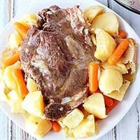 Pot Roast with carrots and potatoes on a white plate