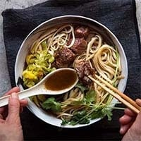 Taiwanese Beef Noodle Soup in a white bowl with fingers holding white soup spoon and chopsticks