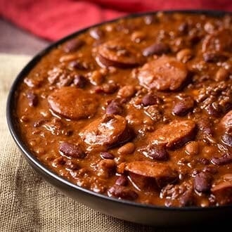 Instant Pot Cowboy Beans are super flavorful, rich and hearty with 3 kinds of meat! These pressure cooker Cowboy Beans can be a main dish or a side. The perfect dish for a pot luck or barbecue! simplyhappyfoodie.com #instantpotcowboybeans #instantpotbakedbeans #Pressurecookercowboybeans #pressurecookerbakedbeans