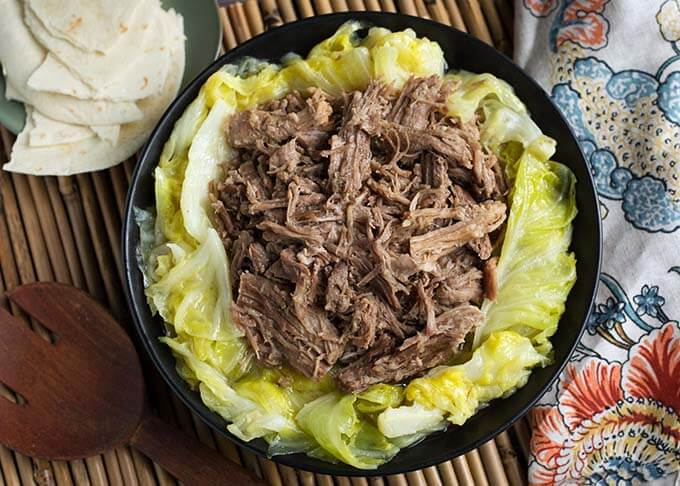Top view of Kalua Pork on cooked cabbage on a black plate