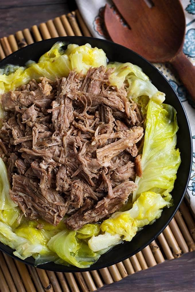 Kalua Pork over cooked cabbage on a black plate