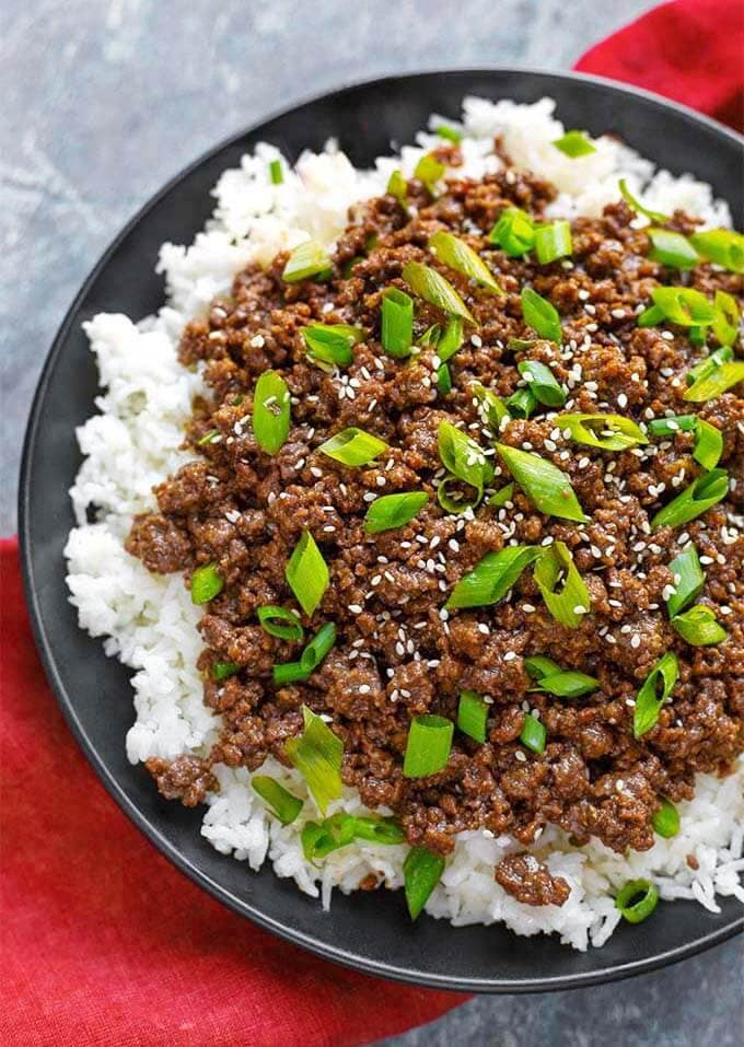 Korean Ground Beef over rice on a black plate
