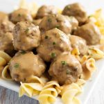 Swedish Meatballs over noodles on a white plate