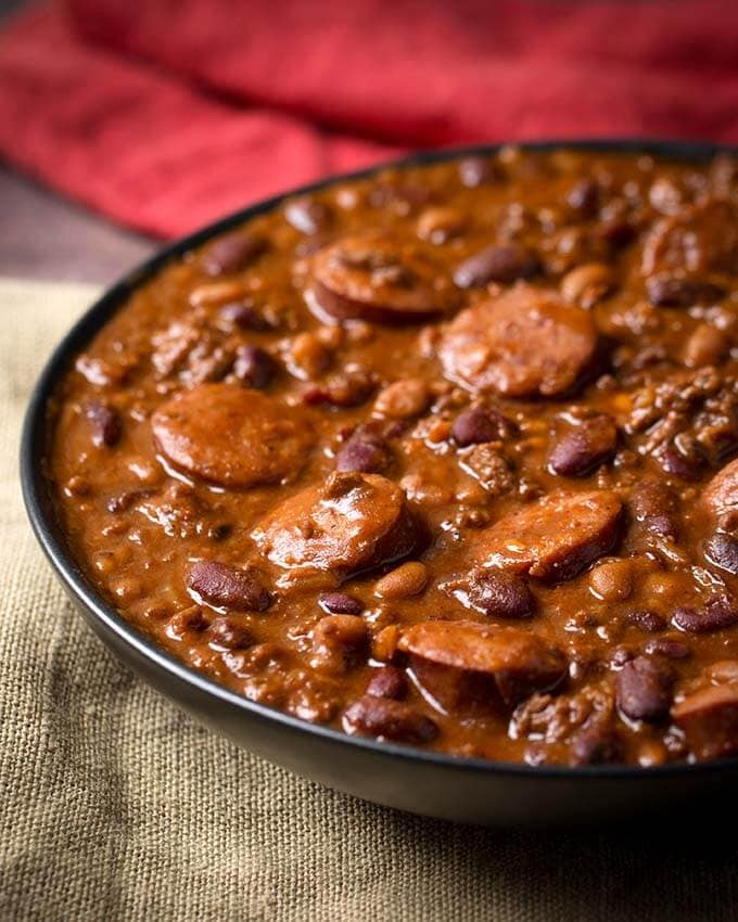 Instant Pot Cowboy Beans are super flavorful, rich and hearty with 3 kinds of meat! These pressure cooker Cowboy Beans can be a main dish or a side. Perfect for a pot luck or barbecue! simplyhappyfoodie.com #instantpotrecipes #instantpotcowboybeans #instantpotbakedbeans #Pressurecookercowboybeans #pressurecookerbakedbeans