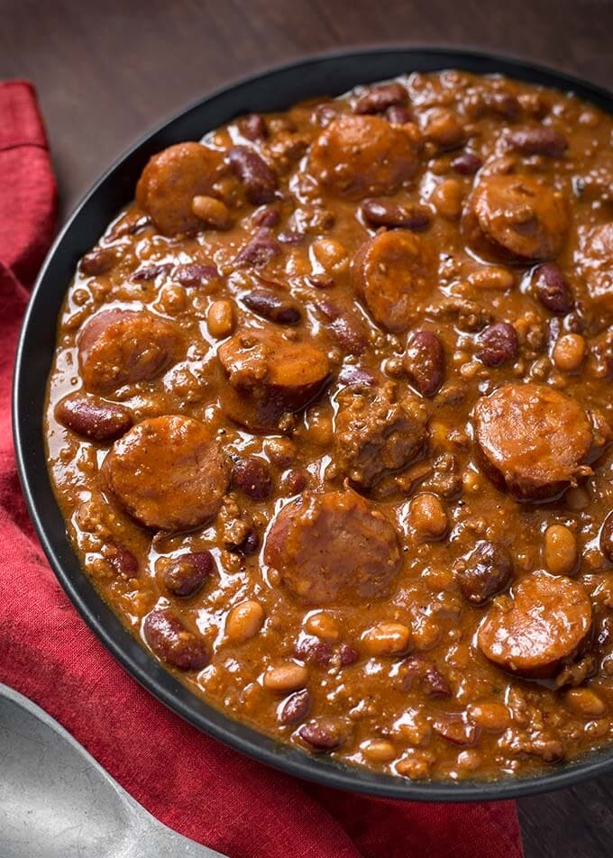 Instant Pot Cowboy Beans are super flavorful, rich and hearty with 3 kinds of meat! These pressure cooker Cowboy Beans can be a main dish or a side. Perfect for a pot luck or barbecue! simplyhappyfoodie.com #instantpotrecipes #instantpotcowboybeans #instantpotbakedbeans Pressurecookercowbowbeans #pressurecookerbakedbeans
