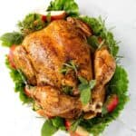 Top view of a cooked Whole Chicken on a white plate with green herbs, leafy vegetables, and apple slices