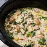 Crock Pot Zuppa Toscana Sausage Potato Soup is rich and very flavorful. With sausage, potatoes, bacon, & kale. A tasty, easy slow cooker zuppa Toscana soup. simplyhappyfoodie.com #crockpotzuppatoscana #crockpotsausagepotatosoup #slowcookerzuppatoscana #slowcookersausagepotatosoup #olivegardensoup