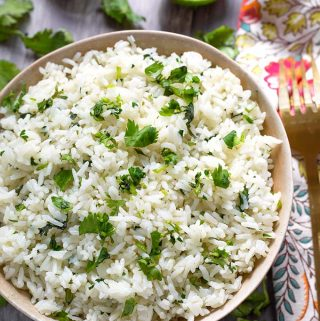 Instant Pot Cilantro Lime Rice is inspired by Chipotle's Cilantro Lime Rice. This delicious pressure cooker cilantro lime rice goes well in tacos, burritos, or rice bowls. Easy and tasty! simplyhappyfoodie.com #instantpotrecipes #instantpotrice #instantpotcilantrolimerice #pressurecookerrice #pressurecookercilantrolimerice