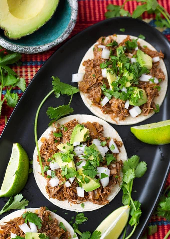 Barbacoa Beef on white corn tortillas topped with chopped avocados, onion and cilantro on a black oblong platter