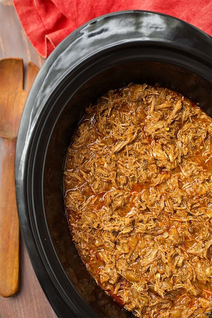 Top view of Barbacoa Beef in a black slow cooker