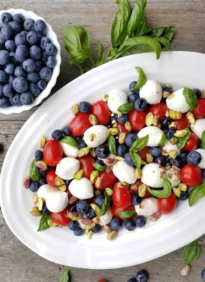 Blueberry Caprese Salad on a white platter next to a bowl of blueberries