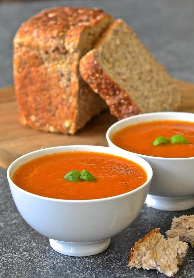 Two bowls of easy tomato basil soup in front of a loaf of bread on a wooden cutting board