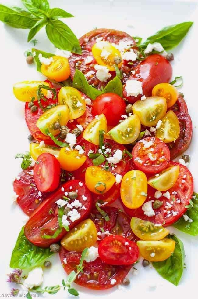 Heirloom Tomato salad with Basil Capers Feta on a white plate