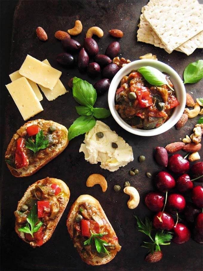 Ratatouille in a small white bowl with some spread on french bread on a platter with different cheeses, olives, cherries, and nuts