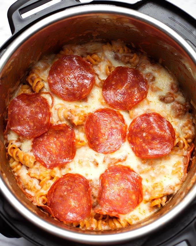 Instant Pot Pizza Pasta Casserole is a delicious, hearty one-pot meal. You can make this pressure cooker pizza pasta casserole with your favorite pizza toppings, and in under an hour! Pizza in a pot! simplyhappyfoodie.com #instantpotrecipes #instantpotpizzapastz #pressurecookerpizzapasta pizza pasta casserole, pizza bake, instant pot pasta recipes