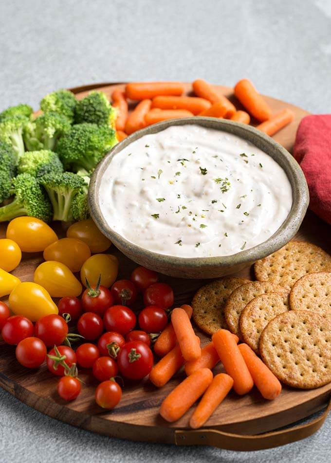 Ranch Vegetable Dip in a gray bowl on a round wooden board surrounded by vegetables and crackers
