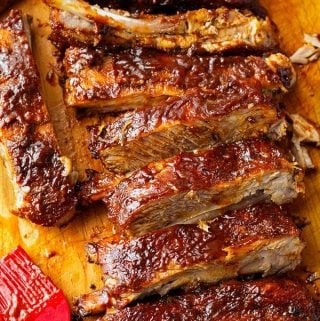 Slow Cooker Ribs are fall off the bone tender, and have amazing flavor. These crock pot ribs are super easy to make, and will quickly become a family favorite! simplyhappyfoodie.com #slowcookerribs #crockpotribs slow cooker barbecue ribs, crock pot barbecue ribs