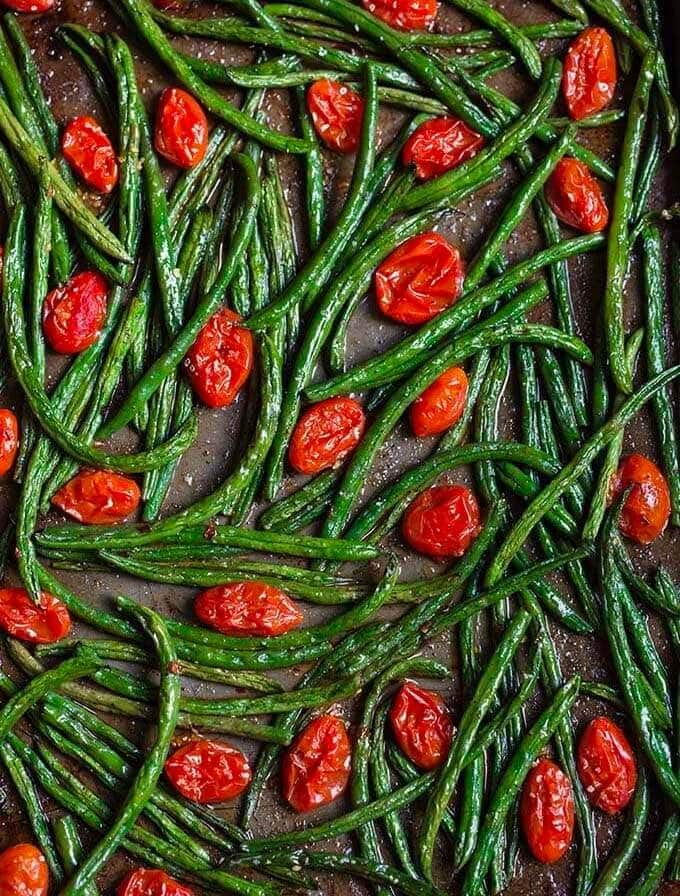 spicy roasted green beans tomatoes on a baking sheet