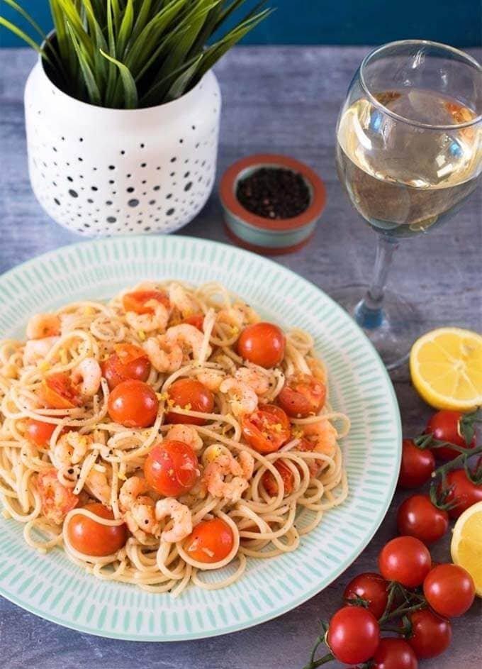 Tomato, garlic, and prawn spaghetti on a white and turquoise plate next to cherry tomatoes and potted plant