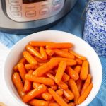 Cinnamon Glazed Carrots in a white bowl in front of a pressure cooker
